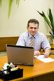 Businessman. Smiling Businessman seated at desk in office setting royalty free stock photos