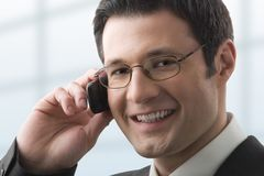 Businessman. The businessman in points smiles and speaks by a mobile phone Royalty Free Stock Photography