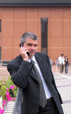 Businessman. Speaking to the mobile phone-main focus on the hand,the people and the building in the distance are intentionally blurred-the persons are not Stock Photo