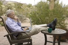Businessman. Senior businessman with laptop on patio working from upscale home in the desert Royalty Free Stock Images