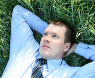 Businessman. Relaxing in the grass on meadow Royalty Free Stock Photos
