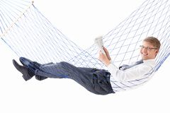 Businessman. Young businessman reading a newspaper in a hammock isolated royalty free stock image