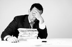 Businessman. A buninessman is frustrated by the pile of bills he has got royalty free stock photography