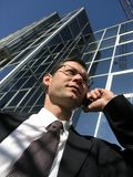 Businessman. Business call. Young businessman talking to the cell phone in front of an office stock photography