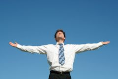 Businessman. Standing with arms outstretched against blue sky Royalty Free Stock Photos
