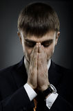Businessman. Portrait  the  businessman careerist in black costume grieve and praying Royalty Free Stock Photography