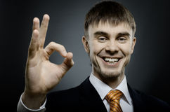 Businessman. Horizontal portrait  the  beautiful  businessman in black costume , to give hand gesture ok Stock Photography