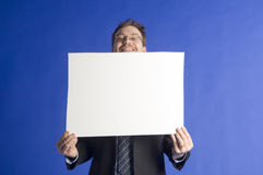 Businessman. Holding a blank white cardboard and peaking behind Stock Photos
