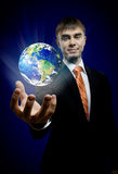 Businessman. Hold in hand terrestrial globe, on dark blue background,  business concept Royalty Free Stock Images