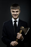 Businessman. Portrait  the  beautiful  businessman  in black costume and black necktie with axe, sinister look and smile Stock Image