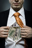 Businessman. Venality businessman or banker  in black costume throw open one's shirt packed heap dollars Royalty Free Stock Photo