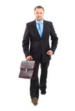 Businessman. Portrait of a happy young business man carrying a suitcase on white background Royalty Free Stock Photo