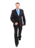 Businessman. Young businessman is walking. He is smiling and looking to the camera.  over white background Royalty Free Stock Photos