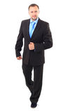 Businessman. Young businessman is walking. He is smiling and looking to the camera. isolated over white background Stock Images