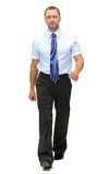 Businessman. Young businessman is walking. He is smiling and looking to the camera. isolated over white background Stock Photos