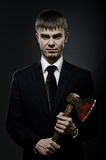 Businessman. Portrait  the   businessman  in black costume and black necktie with axe, sinister look Stock Images