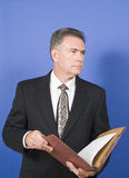 Businessman. A businessman, standing in front of a blue background, reviewing or conducting a briefing on the contents of the folder Royalty Free Stock Image