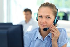 Businessman. Female customer support operator with headset and smiling Royalty Free Stock Images