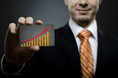 Businessman. In black costume and orange necktie reach out on camera and show credit card  with gold coins and red arrow up, close up Stock Photos