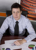 Businessman. Working through his graphs looking at the camera Royalty Free Stock Photos