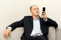 Businessman. With mobile phone sitting at sofa Royalty Free Stock Image