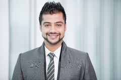 Businessman. Young Asian Indian businessman standing on office background Royalty Free Stock Photos
