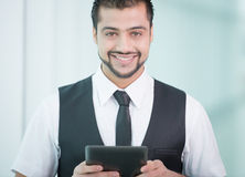 Businessman. Young Asian Indian businessman standing on office background and holding a tablet in hands Stock Photos