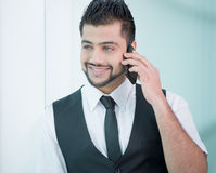 Businessman. Young Asian Indian businessman standing on office background and talking on the phone Stock Photo