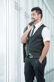 Businessman. Young Asian Indian businessman standing on office background Royalty Free Stock Images