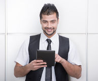 Businessman. Young Asian Indian businessman standing on office background and holding a tablet in hands Royalty Free Stock Photography