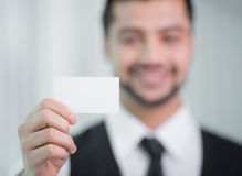 Businessman. Indian businessman holding business card, focus on hand in the office Stock Images