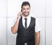 Businessman. Young Asian Indian businessman standing on office background and talking on the phone Stock Photography
