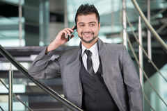 Businessman. Young Asian Indian businessman standing on office background and talking on the phone Royalty Free Stock Photos