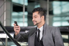 Businessman. Young Asian Indian businessman standing on office background and talking on the phone Royalty Free Stock Images
