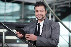 Businessman. Young Asian Indian businessman standing on office background and holding a tablet in hands Stock Images