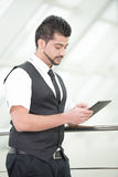 Businessman. Young Asian Indian businessman standing on office background and holding a tablet in hands Royalty Free Stock Photo