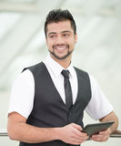 Businessman. Young Asian Indian businessman standing on office background and holding a tablet in hands Royalty Free Stock Photos