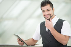 Businessman. Young Asian Indian businessman standing on office background and holding a tablet in hands Stock Photography