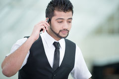 Businessman. Young Asian Indian businessman standing on office background and talking on the phone Royalty Free Stock Photography