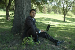 Businessman 4. Businessman in a park with a laptop Royalty Free Stock Photo