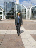 Businessman. Walking with modern corporate building background royalty free stock photography