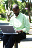 Businessman. An african businessman using laptop in the park royalty free stock image