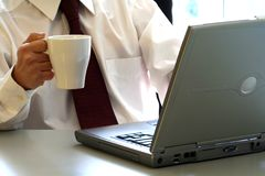 Businessman. A businessman is drinking a cup of coffee and working on his laptop Stock Images