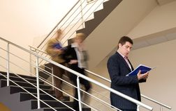 Businessman. Young businessman reading document at the stairs, while other people getting down Royalty Free Stock Images