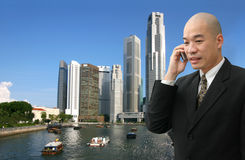 Businessman. Bald Asian Chinese businessman in suit talking on phone with city background stock image