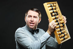 Businessman with abacus. Aggravated businessman holding an old fashioned abacus on black background Stock Images