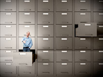 Businessman abstract. Young businessman in file cabinet drawer Stock Photo
