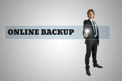 Businessman accessing Online Backup. Stylish young businessman accessing Online Backup by touching a navigation bar on a virtual interface containing the words royalty free stock photos