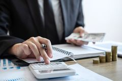 Businessman accountant counting money and making notes at report doing finances and calculate about cost of investment and royalty free stock photos