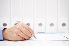Businessman or accountant is signing document with binders in ba Stock Images